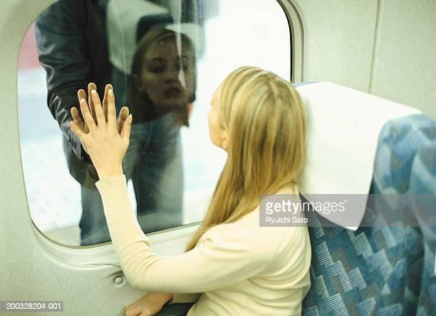 Woman touching fingers of man through train window