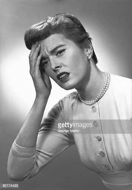 woman touching forehead in studio, (b&w) - donna mezzo busto bianco e nero foto e immagini stock