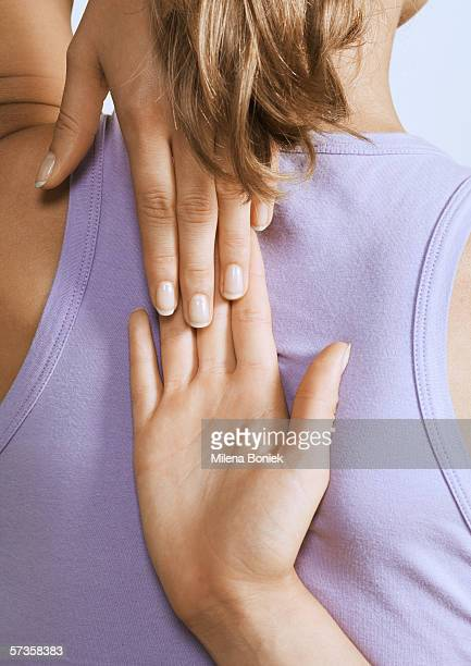 Woman touching hands behind back, close-up