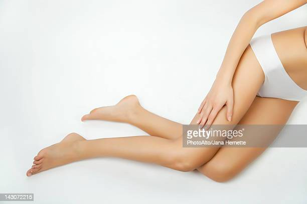 Woman touching her bare leg, cropped