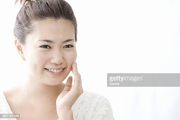 Woman touching her cheek with hand, Tokyo Prefecture, Honshu, Japan