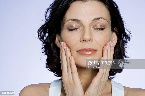 A woman touching her cheeks sensually