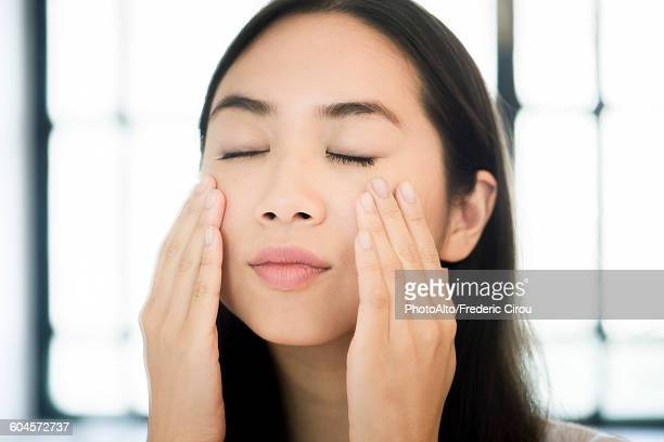 Woman touching her face, eyes closed