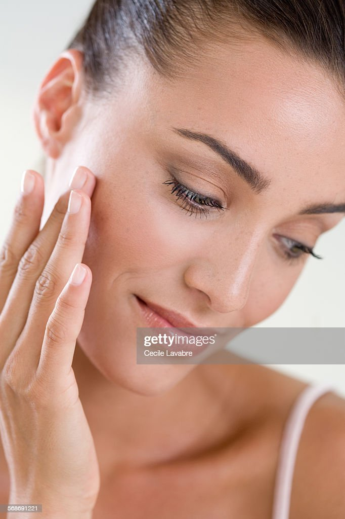 Woman touching her face with finger : Stock Photo