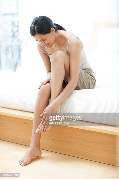 woman touching her foot - womens pretty feet stock pictures, royalty-free photos & images