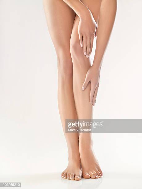 woman touching her legs - womens beautiful feet stock photos and pictures