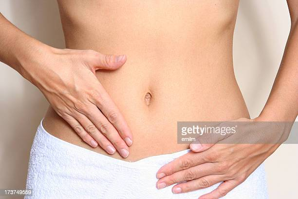 A woman touching her stomach wearing a white towel