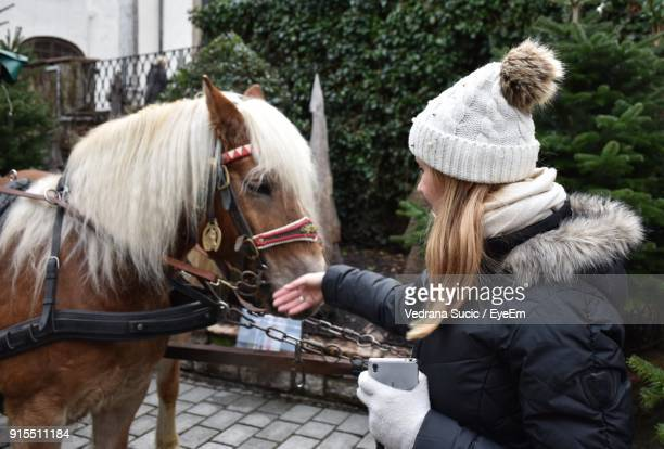 Woman Touching Horse During Winter