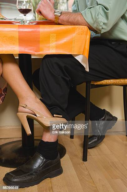 Woman touching mans leg under table