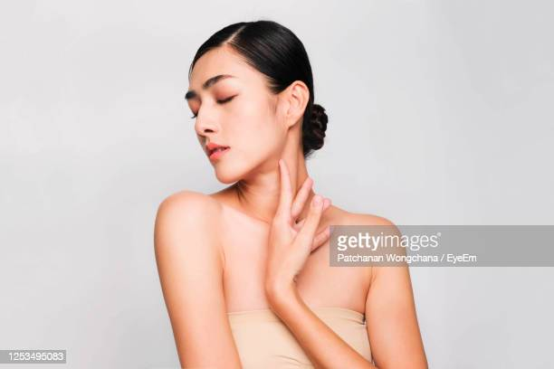 woman touching neck while standing against gray background - beige stock pictures, royalty-free photos & images