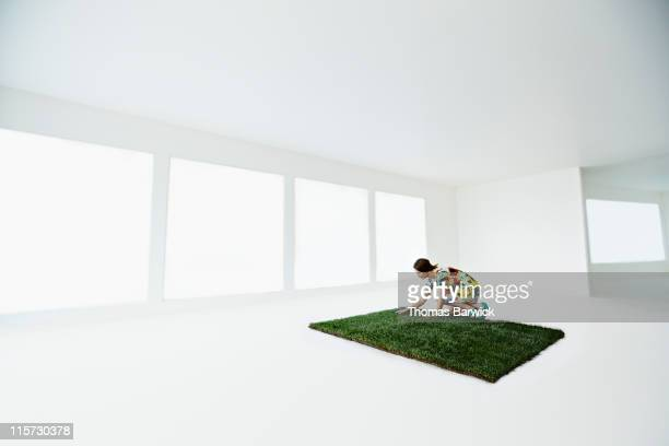 Woman touching patch of grass in empty home