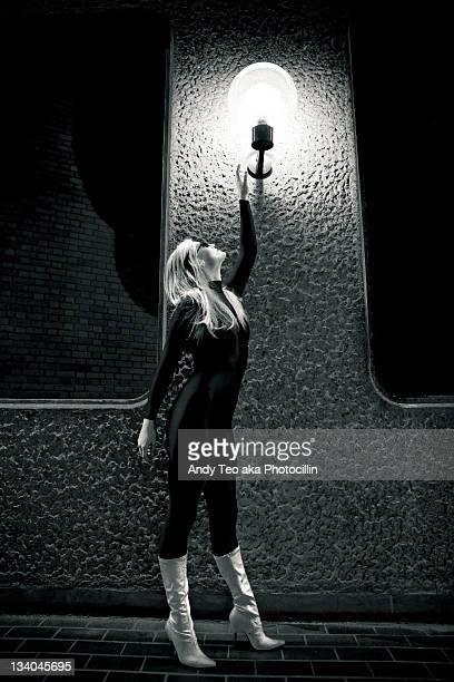 woman touching street lamp - bottes en cuir photos et images de collection