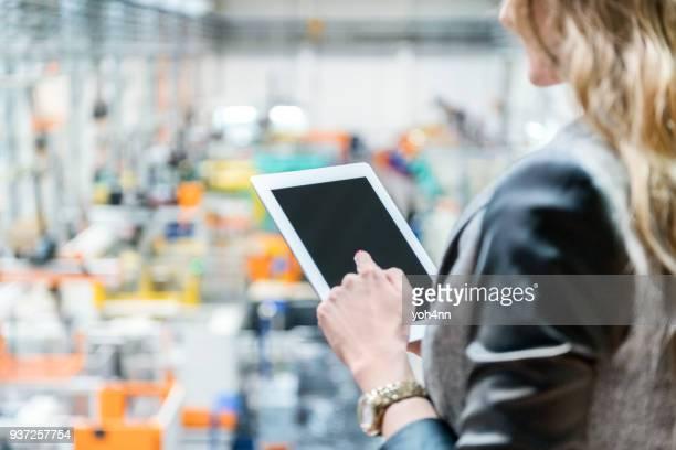Femme, toucher l'écran de la tablette à la chaîne de production