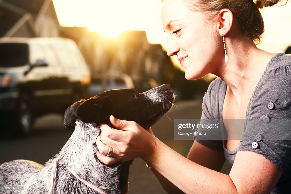A woman touching the neck of her dog : Stock Photo