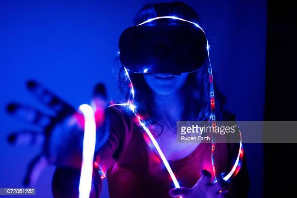 woman touching the virtual space with vr glasses and color led lights - realidade virtual imagens e fotografias de stock