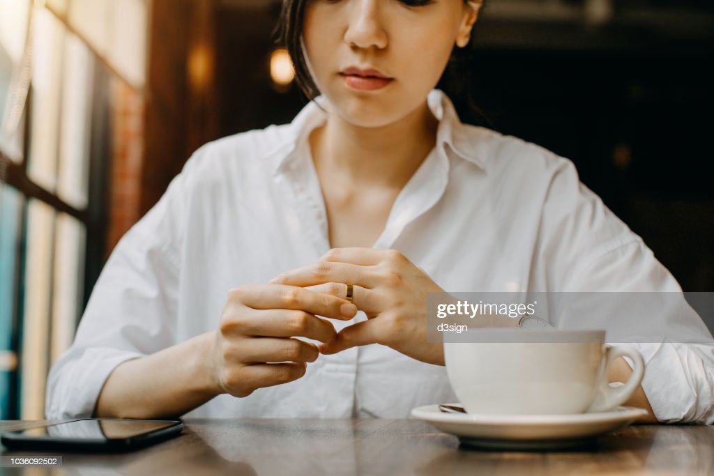 Woman touching the wedding ring on her finger nervously while having coffee and waiting in cafe : Stock Photo