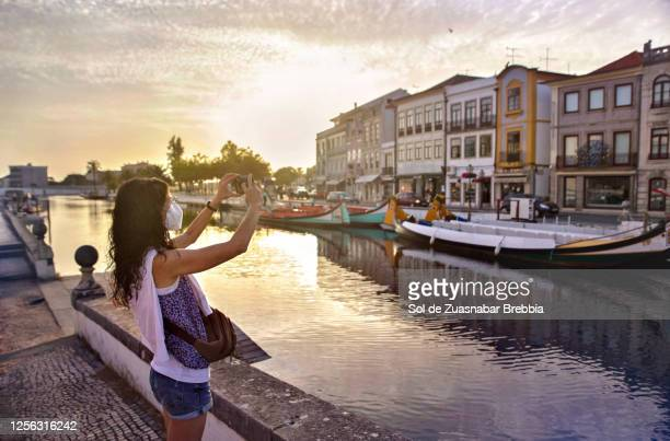 woman touring a beautiful portuguese town, taking photos with her mobile while wearing a mask - アヴェイロ県 ストックフォトと画像