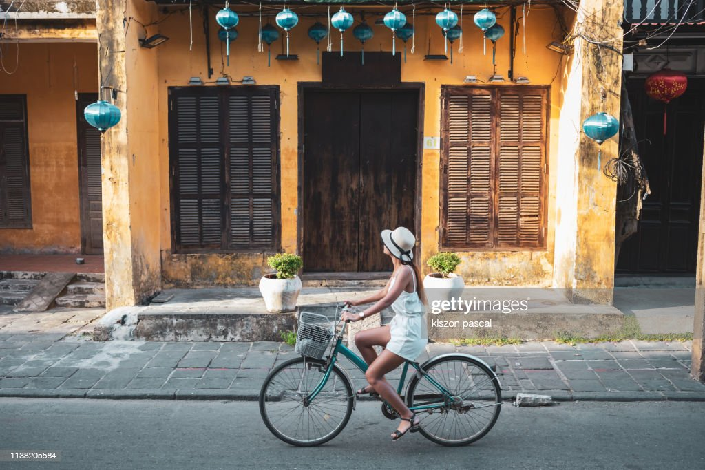 Woman tourist cycling in the old district of Hoi An in Vietnam during day . : Stock Photo