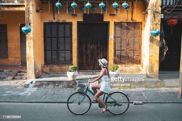 woman tourist cycling in the old district of hoi an in vietnam during day . - reiseziel stock-fotos und bilder