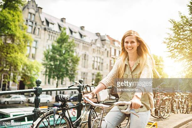 woman tourist cycling on amsterdam - fietsen stockfoto's en -beelden