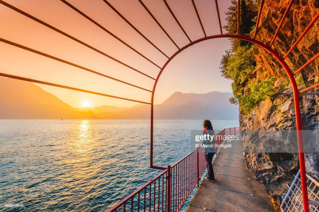 Woman tourist enjoying sunset in Varenna, lake Como, Italy : Stock Photo