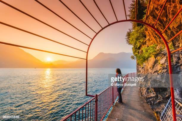 woman tourist enjoying sunset in varenna, lake como, italy - lake como stock pictures, royalty-free photos & images