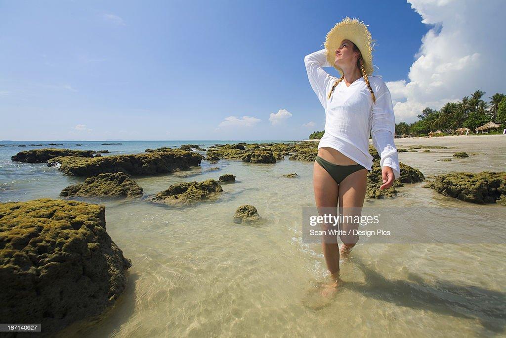 A Woman Tourist Enjoys The Sunshine On The Beach Of A Tropical Island : Stock Photo