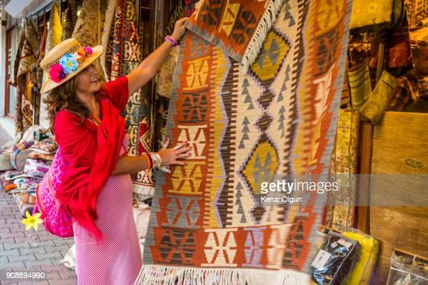 vrouw toeristische kijkt de tapijten in de winkel tapijt. datca, mugla / turkije. - turkey middle east stockfoto's en -beelden