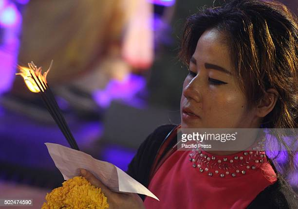 Woman tourist prays at the Erawan Shrine Ratchaprasong during the welcome ceremony of Festival Christmas and New year 2016, at neighborhood shopping...