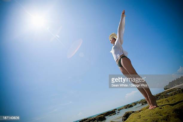 A Woman Tourist Raises Her Arms On The Beach Of A Tropical Island