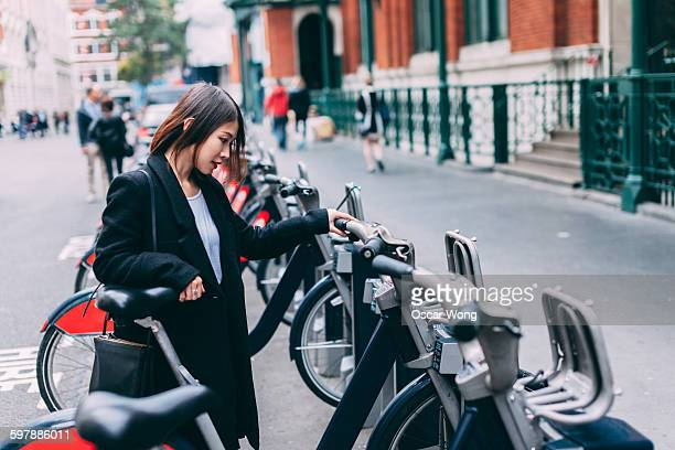 Woman tourist renting bicycle on street in London