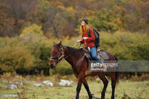 woman tourist rides a horse in the mountains - dressage horse russia stock photos and pictures