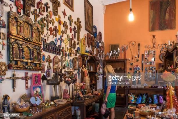 a woman tourist shops for souvenirs in a shop filled with hand made crafts in todos santos, mexico. - todos santos mexico fotografías e imágenes de stock