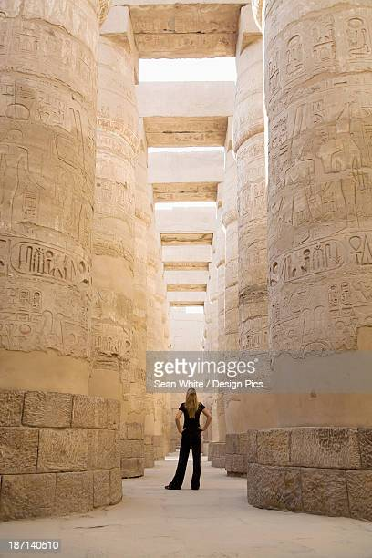 a woman tourist stands at the base of the massive columns in the temples of karnak on the east bank of luxor along the nile river - temples of karnak stock pictures, royalty-free photos & images
