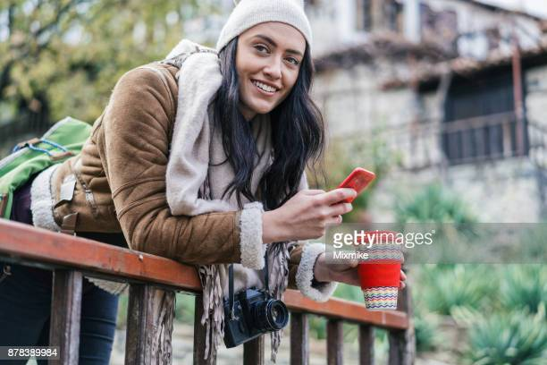 Woman tourist texting on the phone and relaxing