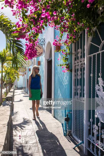 a woman tourist walks along a bougainvillea lined street in todos santos, mexico. - todos santos mexico fotografías e imágenes de stock