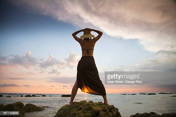 a woman tourist wearing a hat and sarong stands on the beach of a tropical island at sunset - free up skirt pics stock photos and pictures