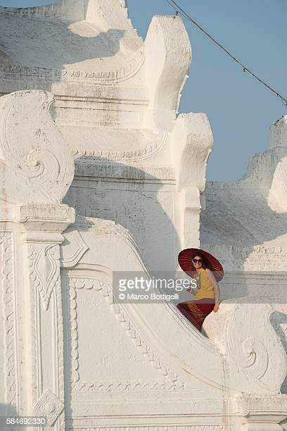 Woman tourist with red umbrella sitting on the Hsinbyume white pagoda.