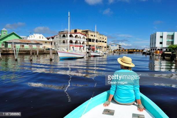 a woman tours through belize city on the bow of a fishing boat - belize stock pictures, royalty-free photos & images
