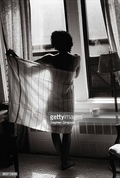 Woman toweling off by windows