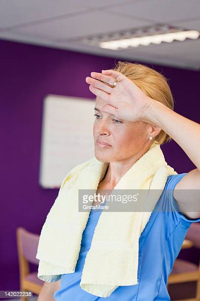 woman toweling off in gym - head in hands stock pictures, royalty-free photos & images