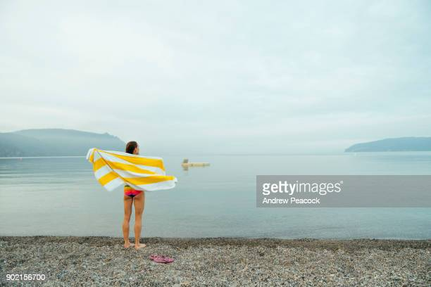 a woman towels off after a dip in lake taupo - lakeshore stock pictures, royalty-free photos & images