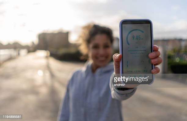 woman tracking her fitness progress on an app while running - activity stock pictures, royalty-free photos & images