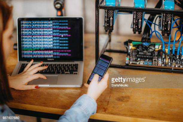 woman trading bitcoin price with a laptop computer by internet - cryptocurrency mining stock photos and pictures