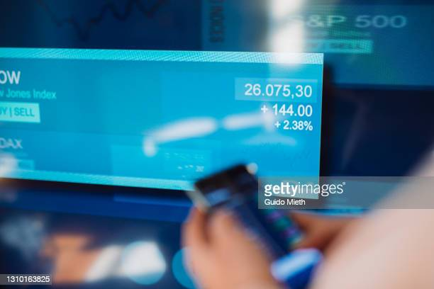 woman trading stock with mobile app in front of stock exchange screen. - stock market stock pictures, royalty-free photos & images
