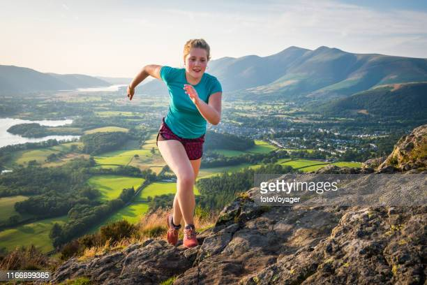 woman trail runner bounding up rocky mountain summer summit - running stock pictures, royalty-free photos & images