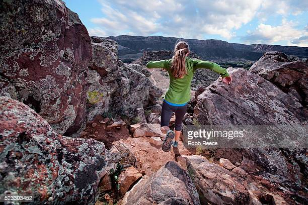 a woman trail runner descending a rocky trail - robb reece stock pictures, royalty-free photos & images
