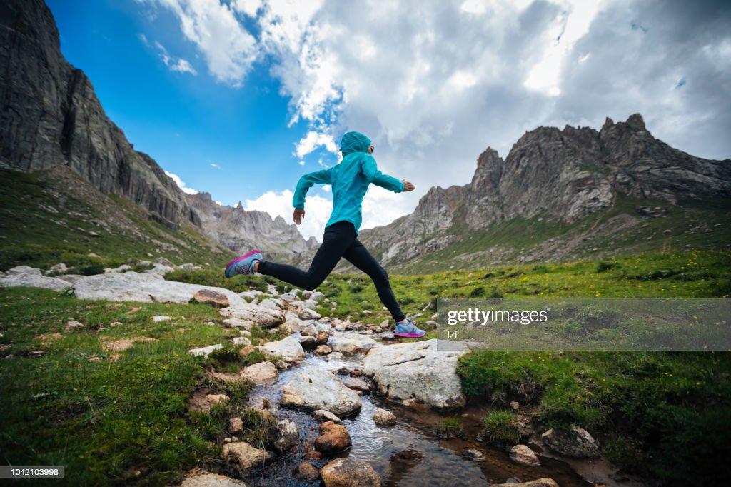 美しい山々 に samll 川を飛び越えて女性トレイル ランナー : ストックフォト