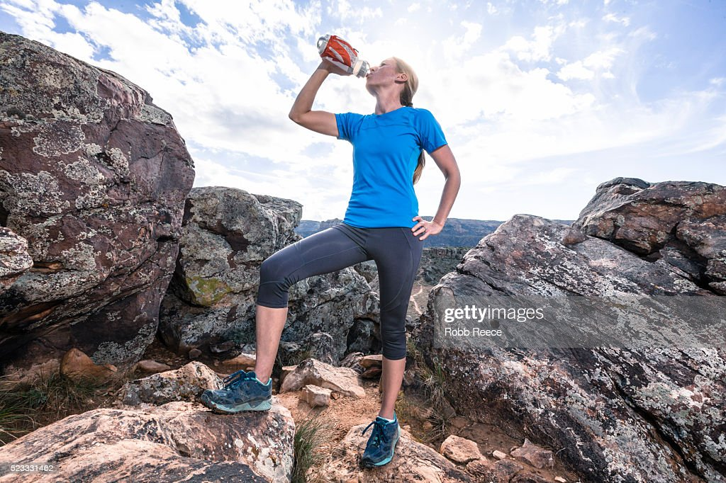 A woman trail runner on a rocky trail drinking from a water bottle : Stock Photo