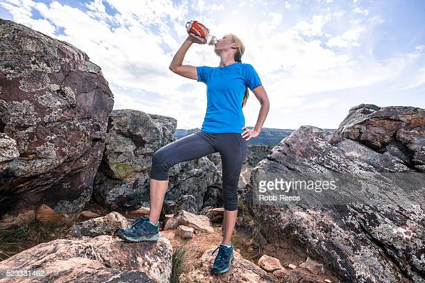 a woman trail runner on a rocky trail drinking from a water bottle - robb reece 個照片及圖片檔